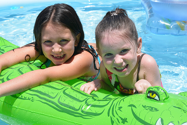 Kids swimming in pool on float