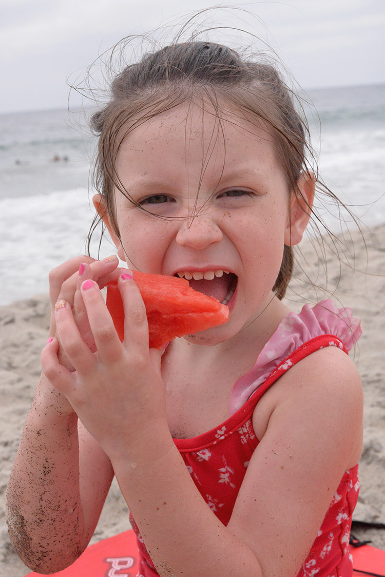 4 year old eating watermelon at beach