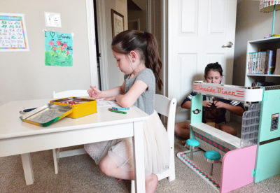 kids playing in room coloring dolls