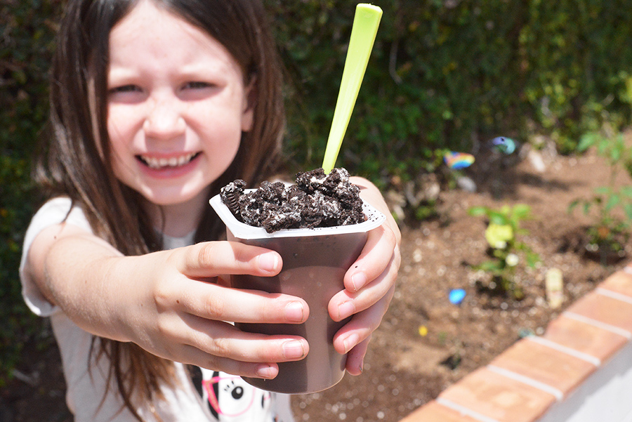 enjoying pudding dirt cup in garden